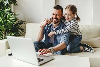 Father and daughter on the sofa looking at a laptop